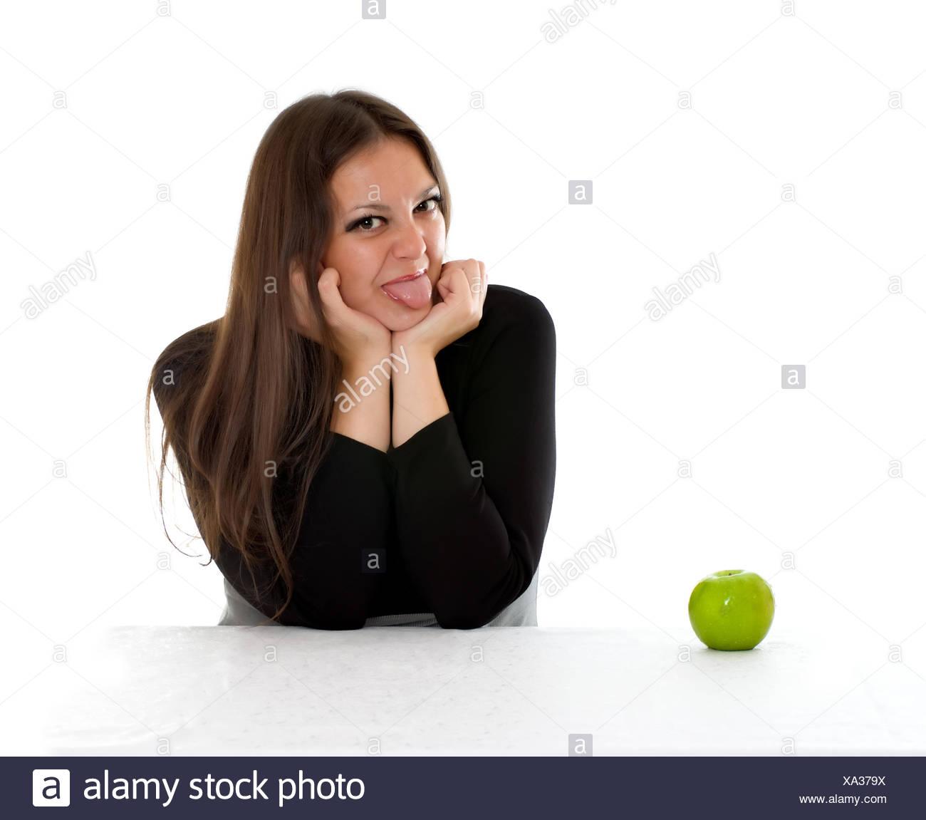 Chica con manzana verde mostrando la lengua Foto de stock