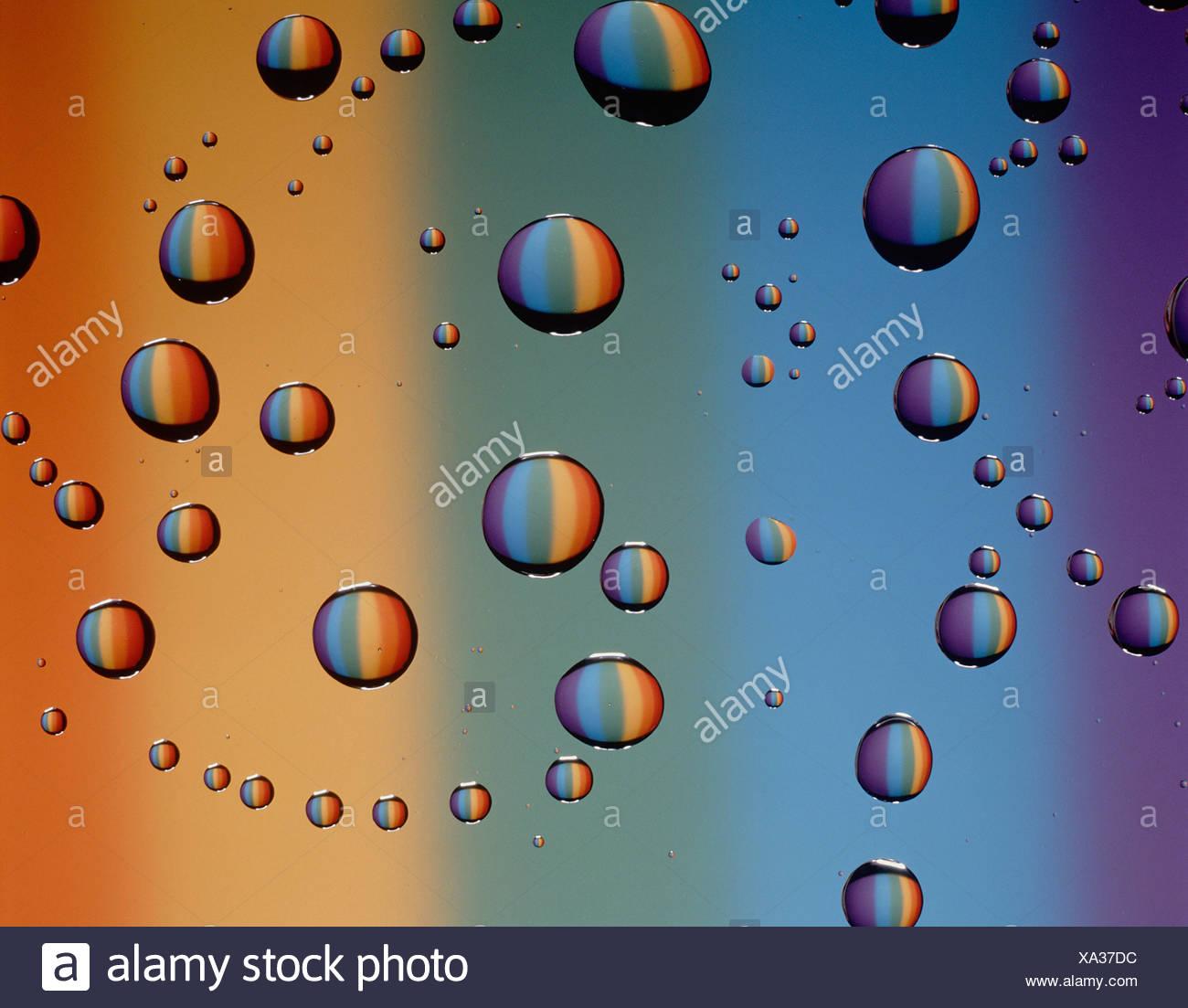 Sigue de cerca la vida de las gotas de agua sobre la superficie del cristal contra el telón de fondo de colores espectrales. Foto de stock