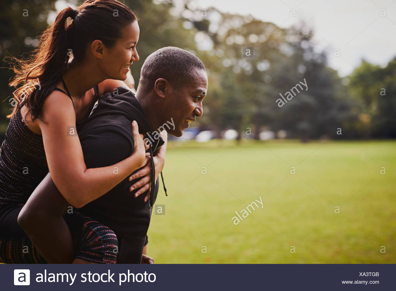 El hombre y la mujer a divertirse en el parque, dando capacitación piggy back Imagen De Stock