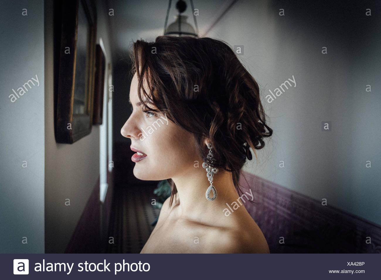 Ver perfil de reflexivas bella mujer en el corredor Imagen De Stock