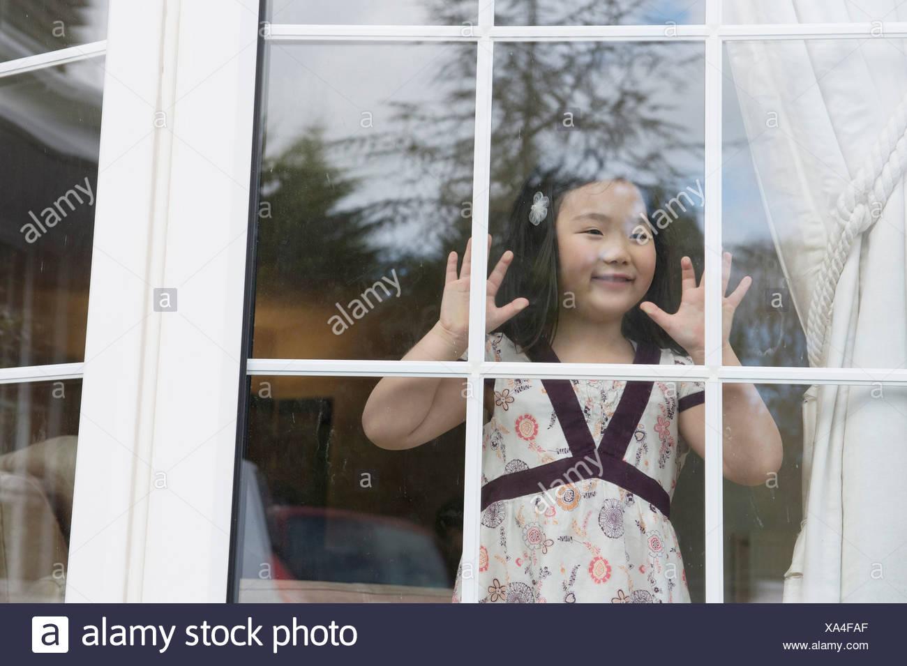 Chica sentada mirando desde la ventana de la habitación Imagen De Stock