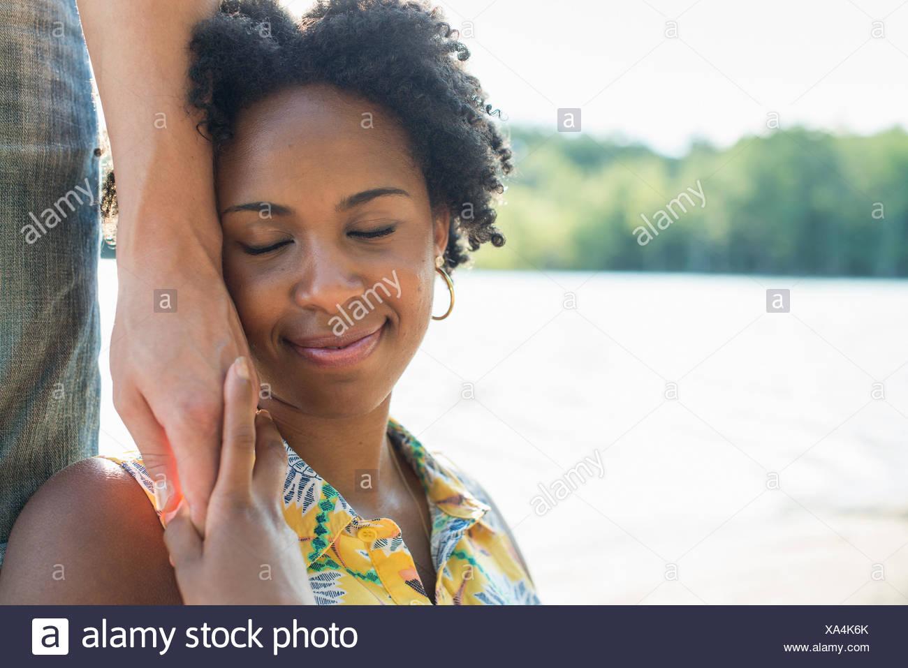 Una mujer sosteniendo la mano de una persona a su mejilla y sonriente. Foto de stock