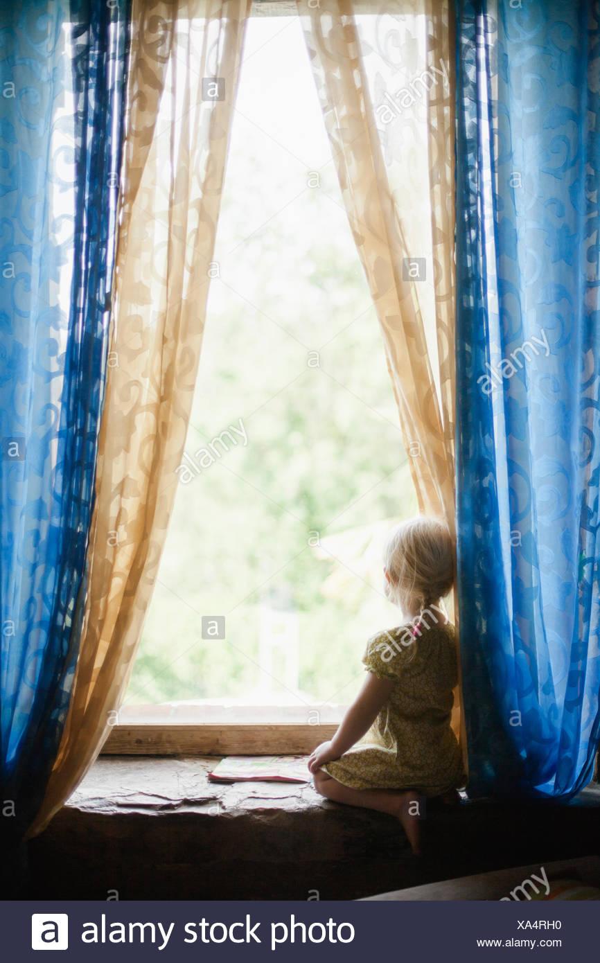 Italia, Toscana, Chica (2-3) mirando a través de la ventana Imagen De Stock