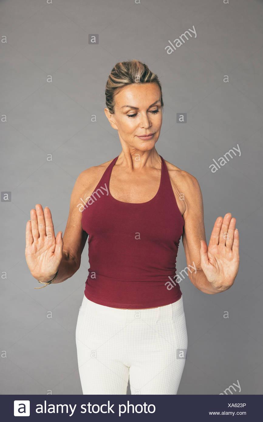 Mujer madura, ejercicios de flexibilidad el codo del brazo y de la mano Imagen De Stock