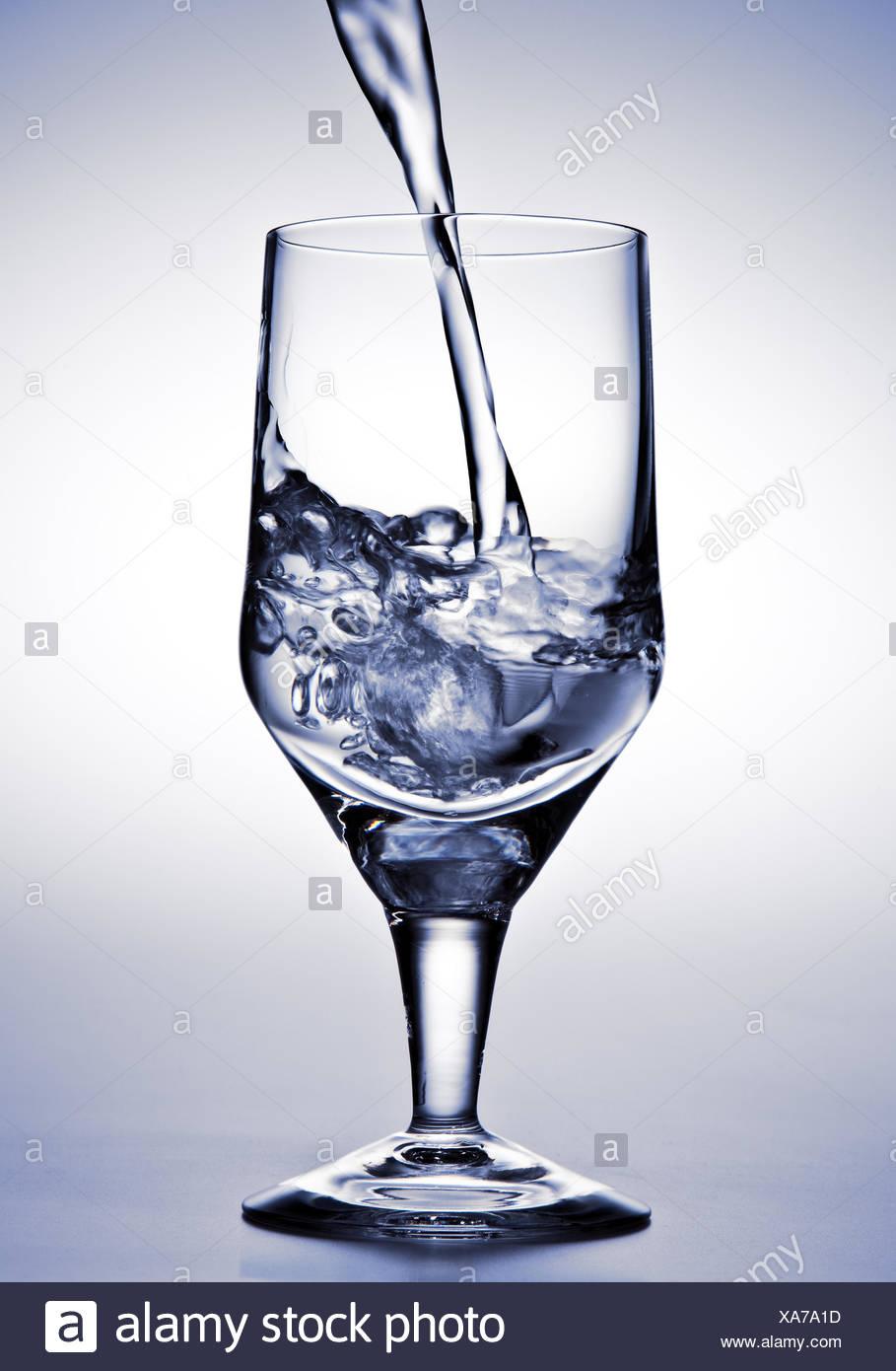 El agua se vierte en un vaso Imagen De Stock