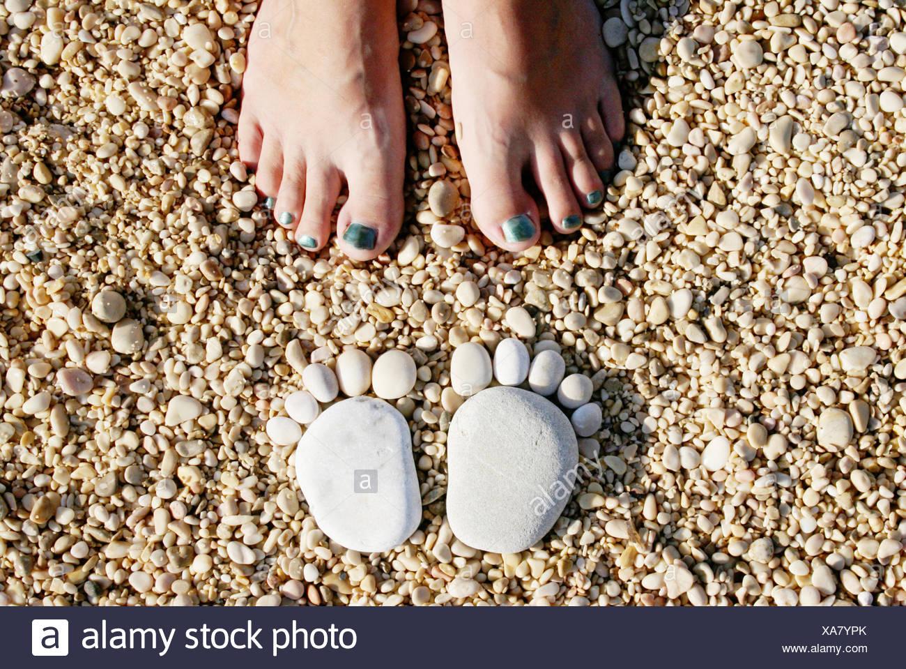 Croacia, piedras en forma de pies delante de los pies de la mujer Imagen De Stock
