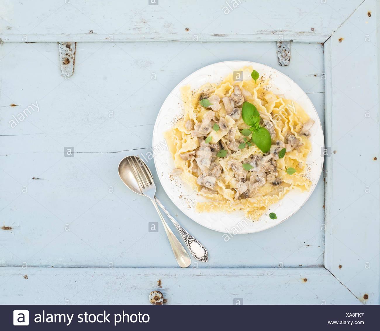 Pasta mafaldine con champiñones y salsa de nata en placa de cerámica blanca sobre fondo azul de madera. Vista desde arriba. Espacio de copia Imagen De Stock