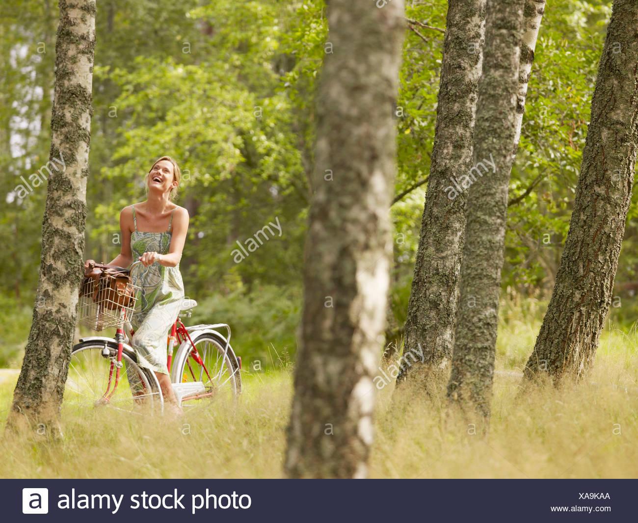 Mujer andar en bicicleta en el bosque sonriente. Imagen De Stock