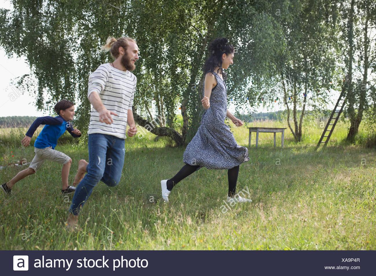 Familia lúdica ejecuta en patio rural Imagen De Stock