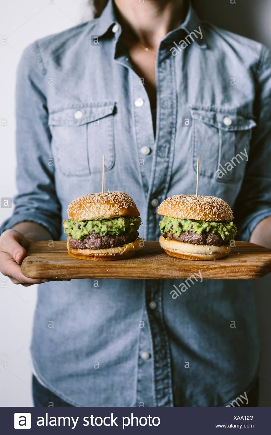 Una mujer es fotografiada desde la vista frontal manteniendo dos guacamole hamburguesas en sus manos sobre una tabla para cortar madera. Imagen De Stock