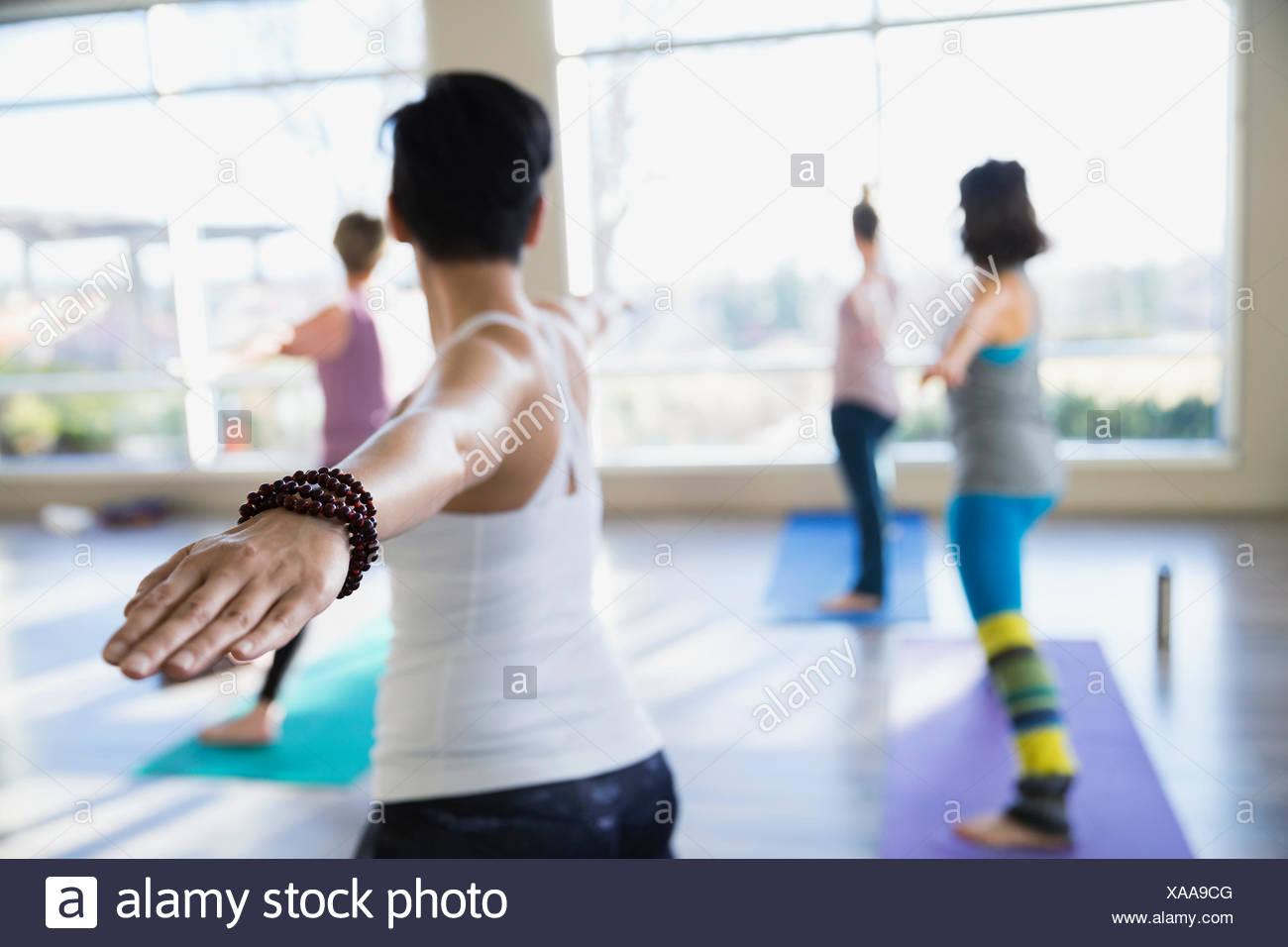 Las mujeres que practican guerrero 2 plantean en clase de yoga Imagen De Stock