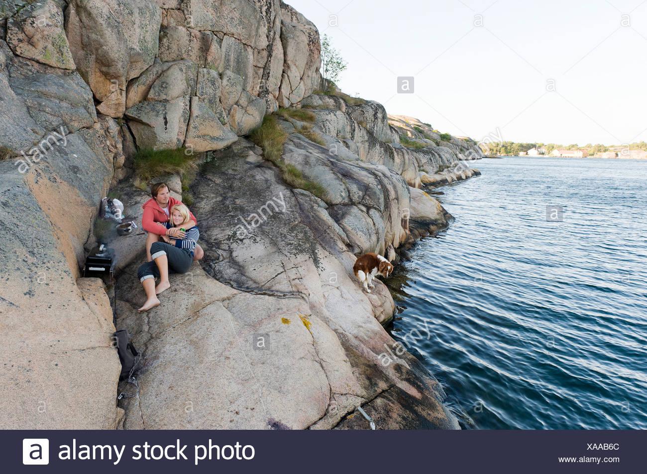 Romántica y relajada muchacho y muchacha adolescente en la roca por el mar pacífico Imagen De Stock