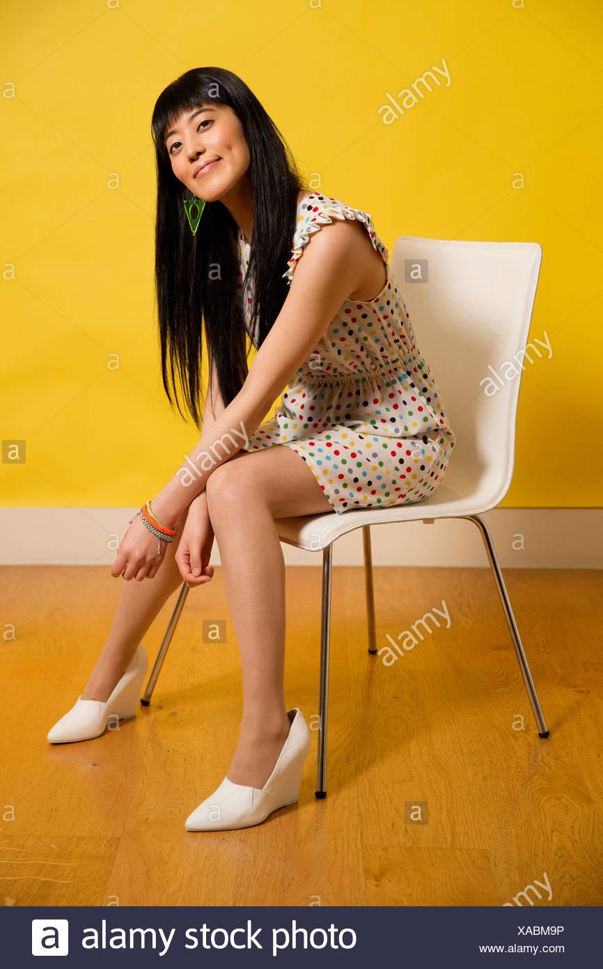e7b1ee626 Retrato de joven mujer vistiendo vestido manchado sentado en una silla  Imagen De Stock