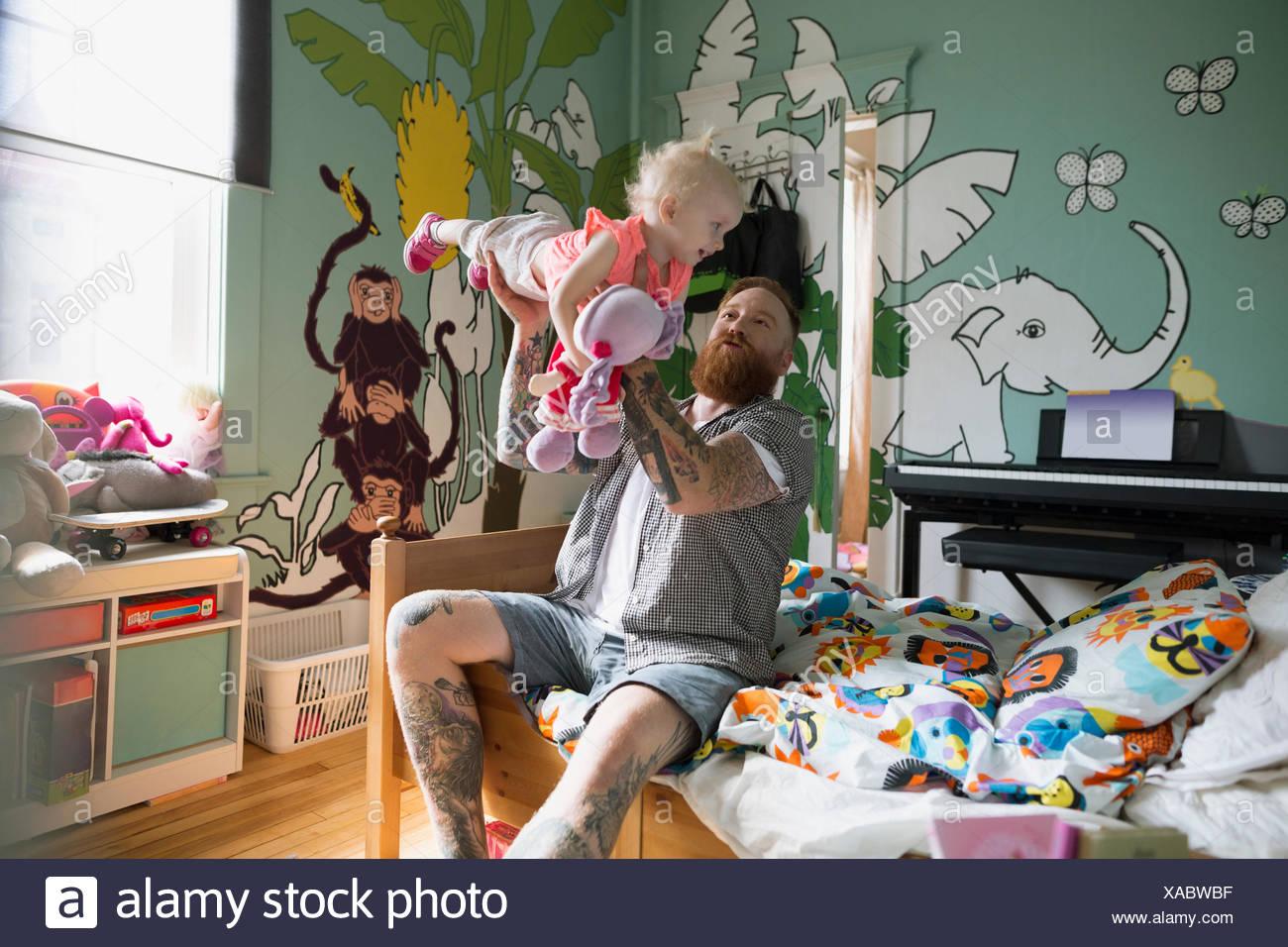 Juguetón Flying Padre hija en dormitorio Imagen De Stock