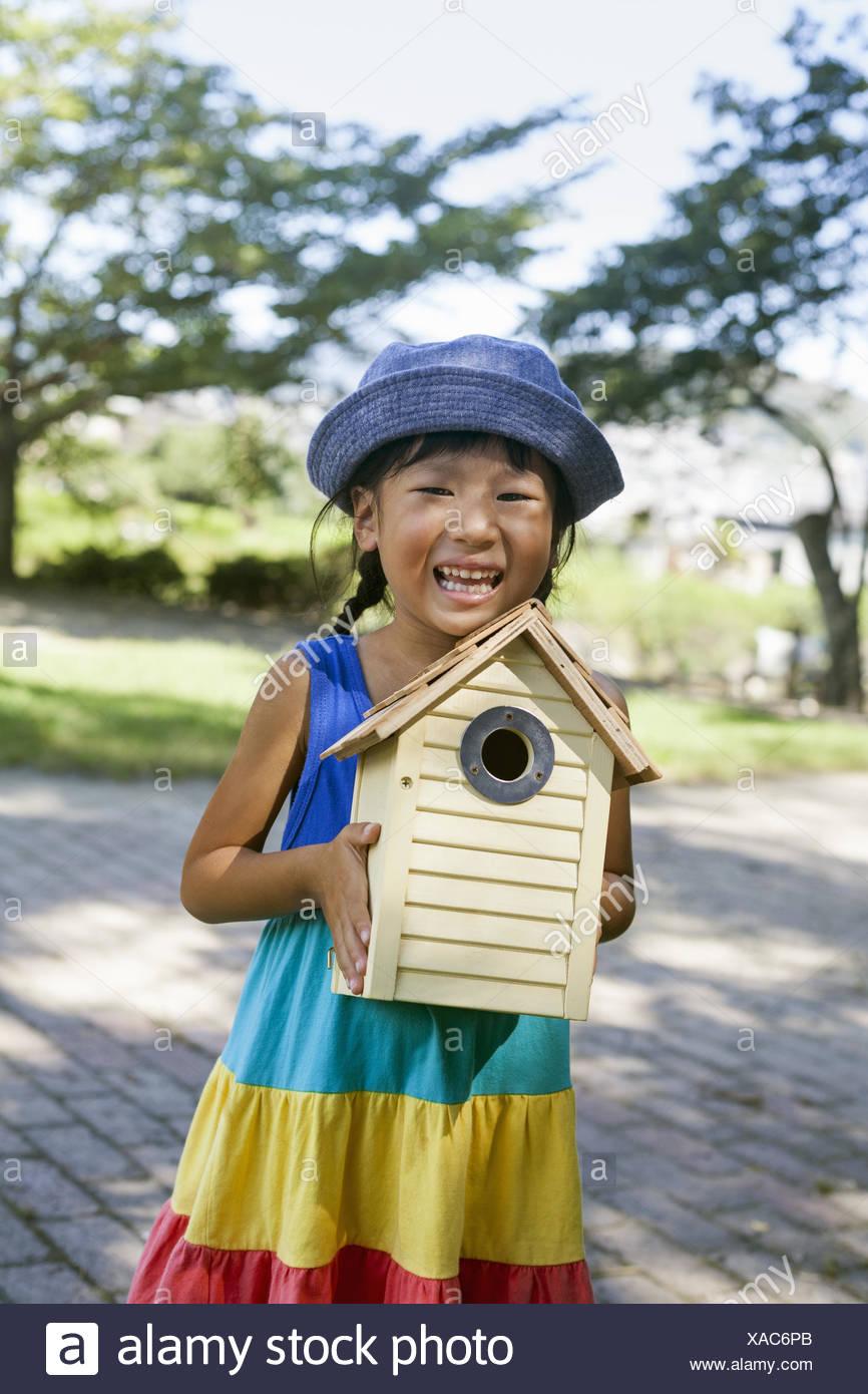 Joven llevando un vestido y sombrero para el sol, sosteniendo una casa de aves. Foto de stock