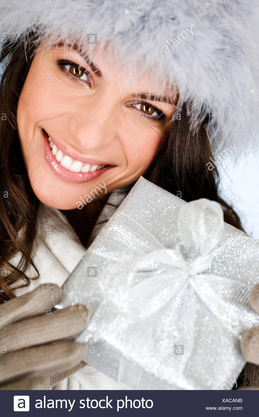 Una joven mujer sosteniendo un regalo de Navidad Imagen De Stock
