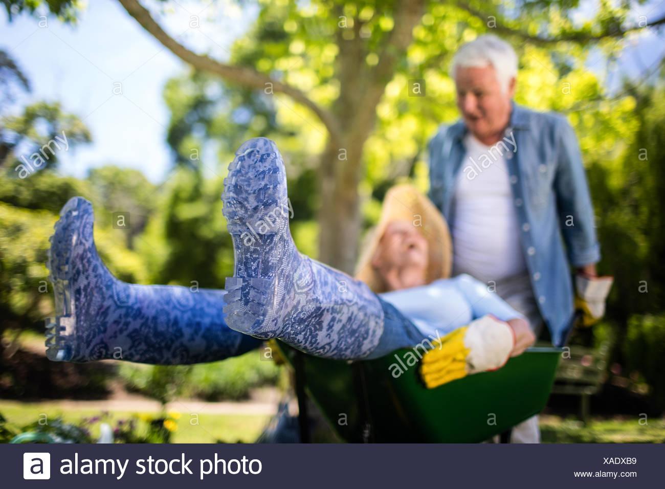 Las parejas ancianas jugando con una carretilla de mano Imagen De Stock