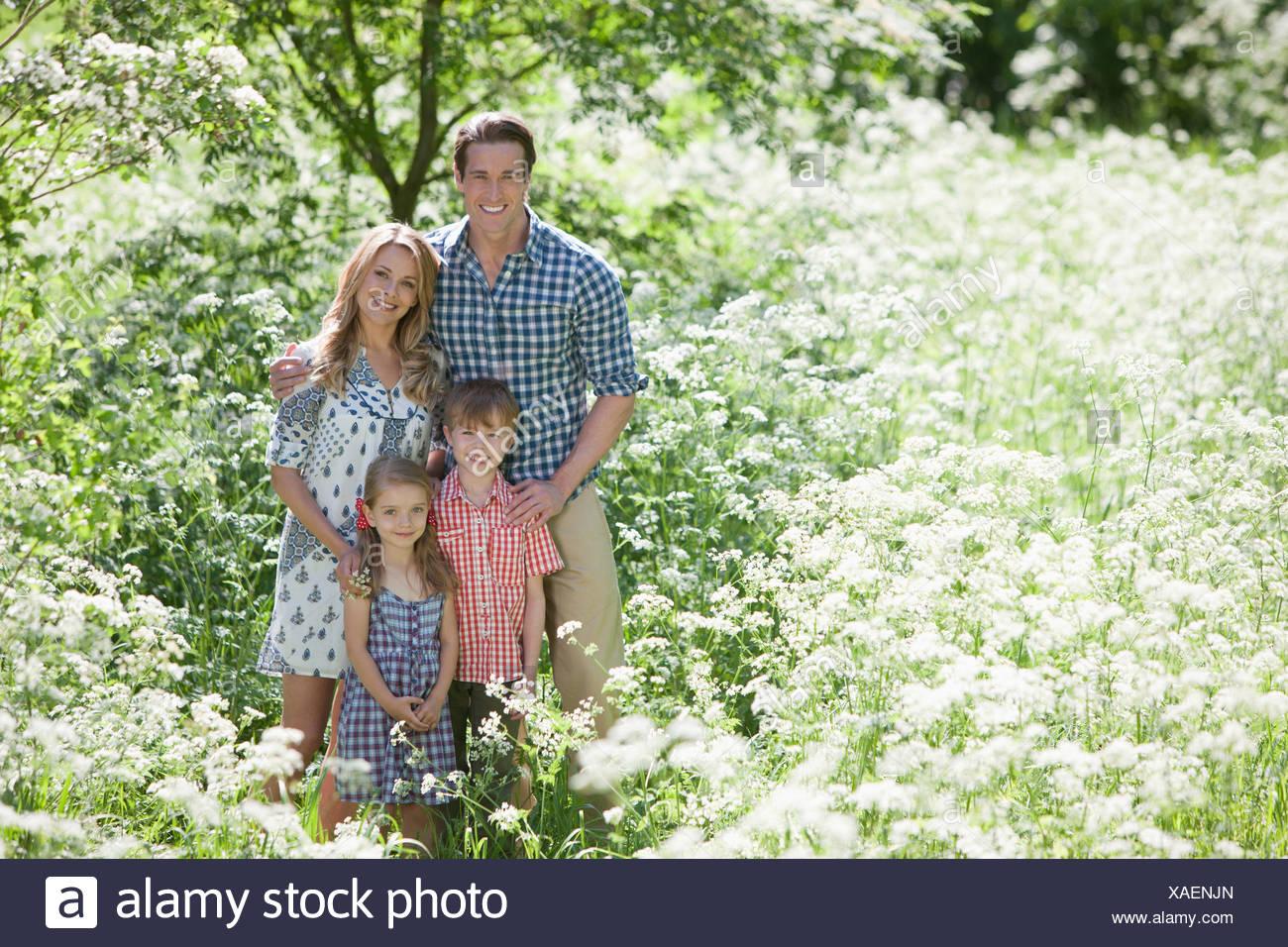 Familia de pie juntos en el campo de las flores Imagen De Stock