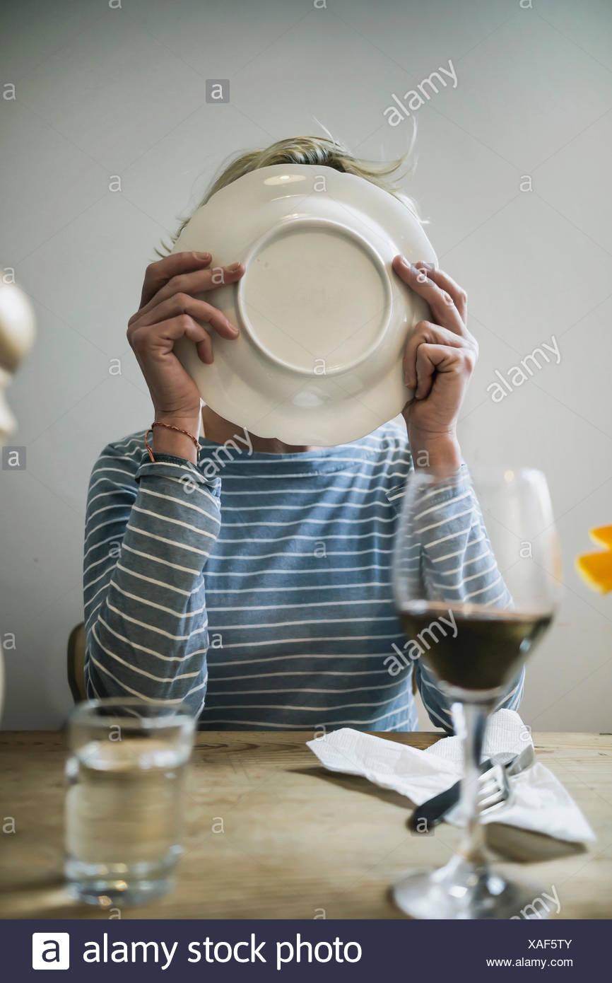 Mujer lamiendo un plato en casa Imagen De Stock