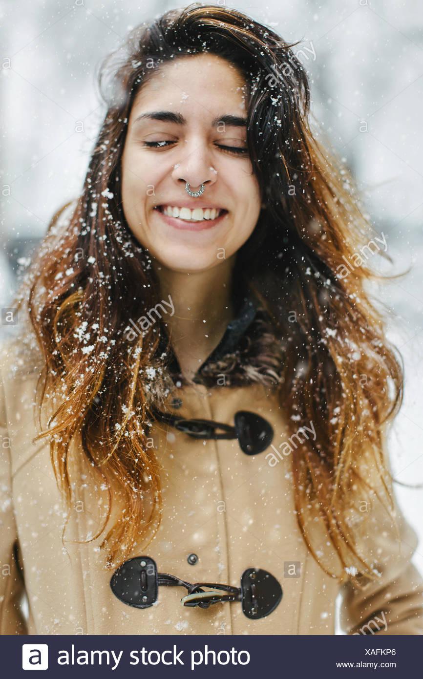 Mujer vistiendo duffle coat en nieve, ojos cerrados sonriendo Imagen De Stock