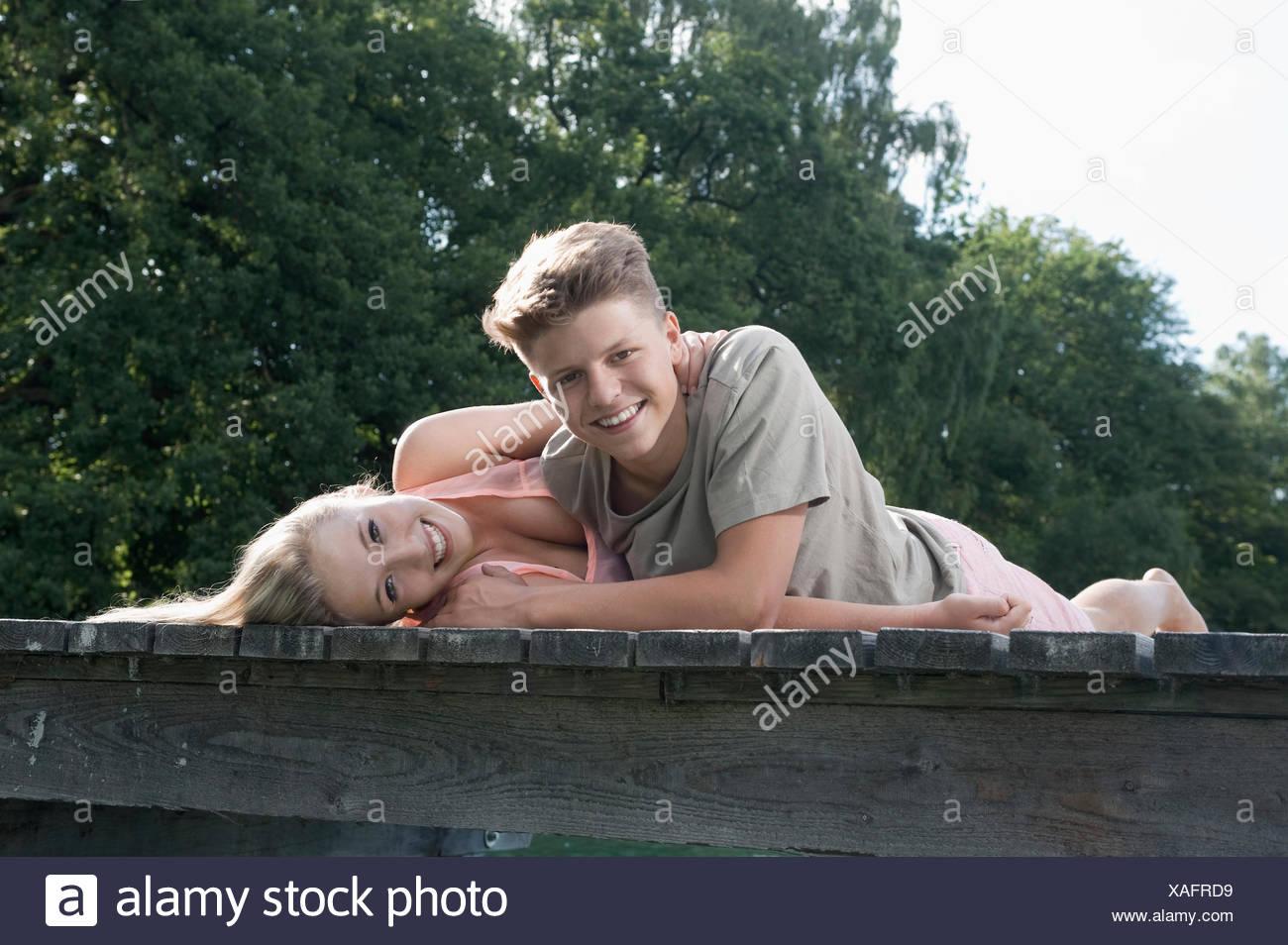 La pareja de adolescentes tumbado sobre un embarcadero en el lago Imagen De Stock