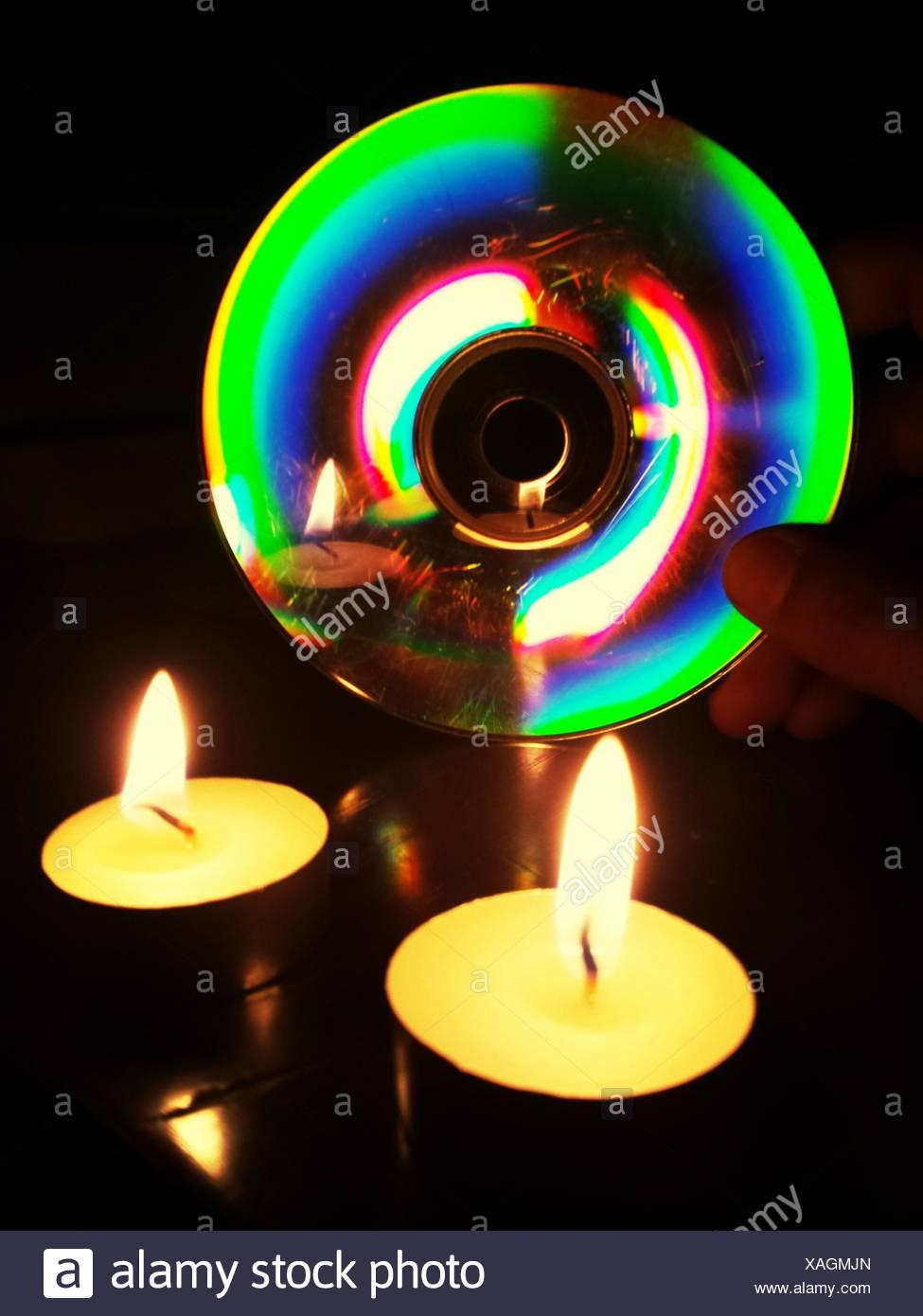 A la luz de las velas que refleja en disco compacto Foto de stock