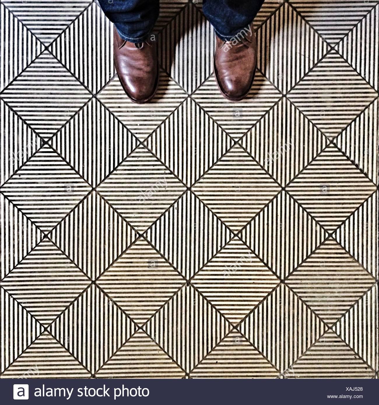 Los pies del hombre sobre el suelo Imagen De Stock