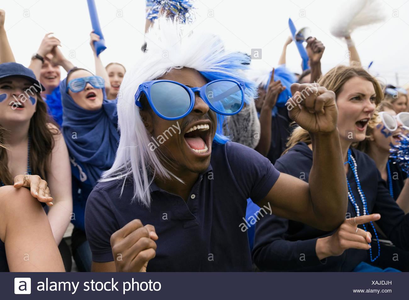 Entusiasta fan en enormes gafas azules vítores Imagen De Stock