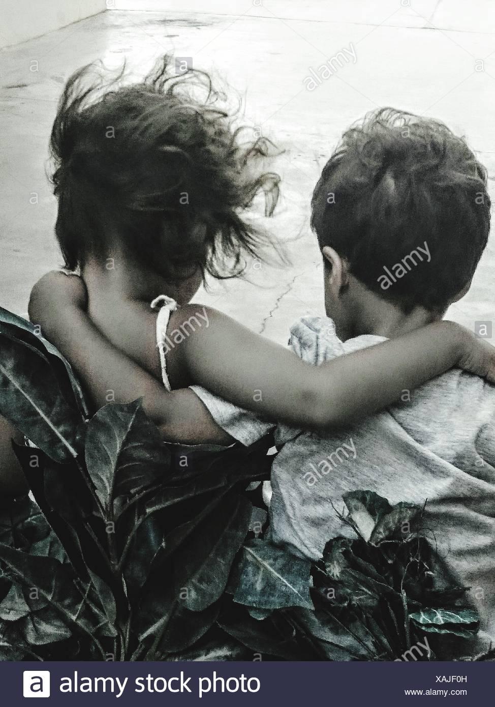 Vista trasera de hermanos con brazo alrededor afuera Imagen De Stock