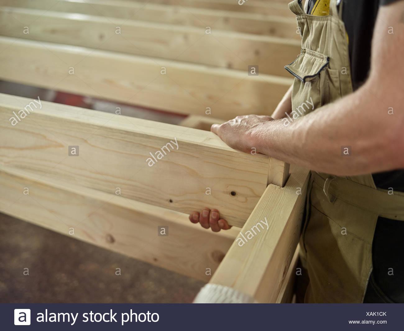 Las manos del hombre conectar dos vigas de madera con ranura y lengüeta de conexión de una construcción de madera, Austria Imagen De Stock