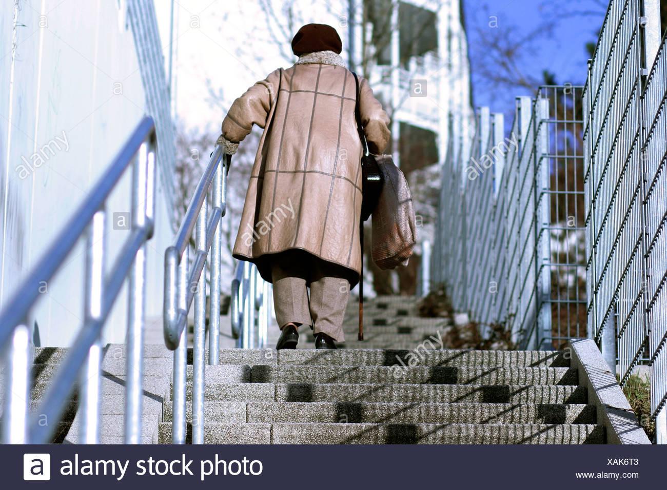 Anciana subiendo las escaleras Imagen De Stock