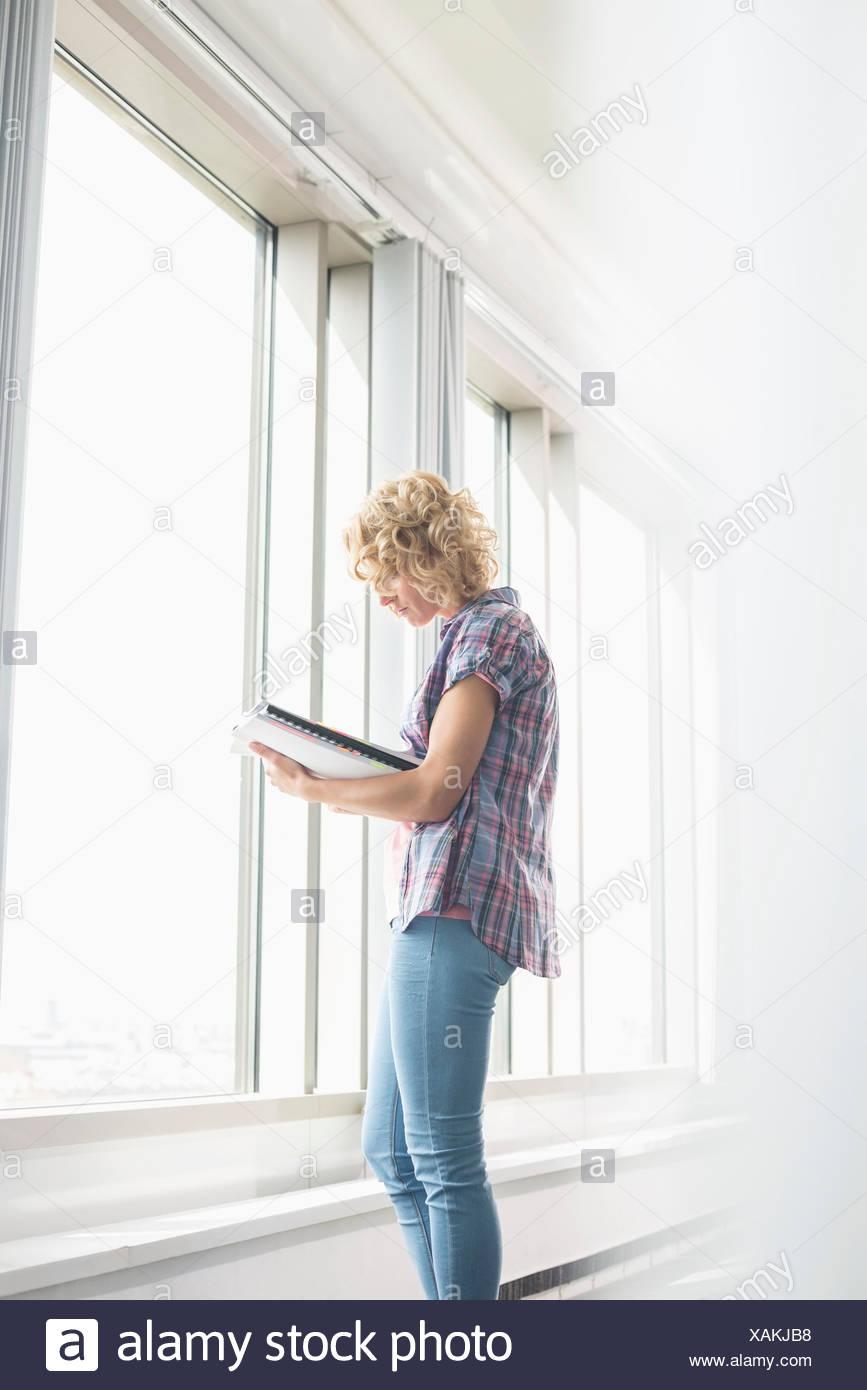 Vista lateral de la empresaria creativa leer el archivo por ventana en la oficina Imagen De Stock
