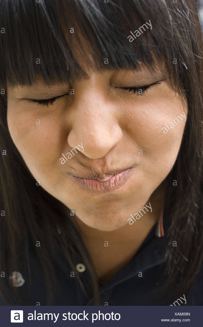 El rostro de un adolescente que hace muecas abultadas mejillas y cerró los ojos Foto de stock