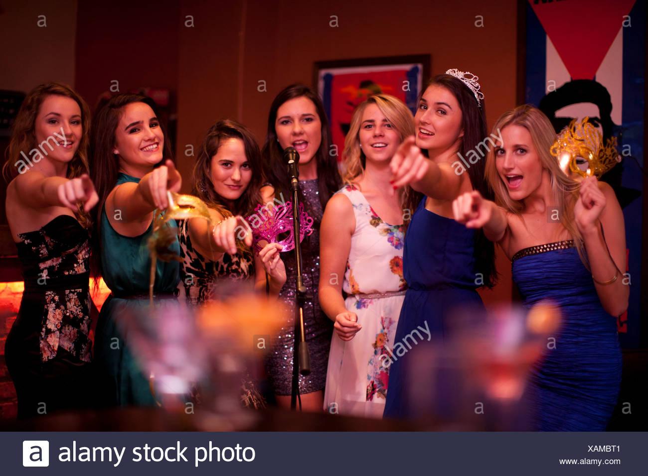 Las mujeres jóvenes cantando en el bar karaoke Imagen De Stock