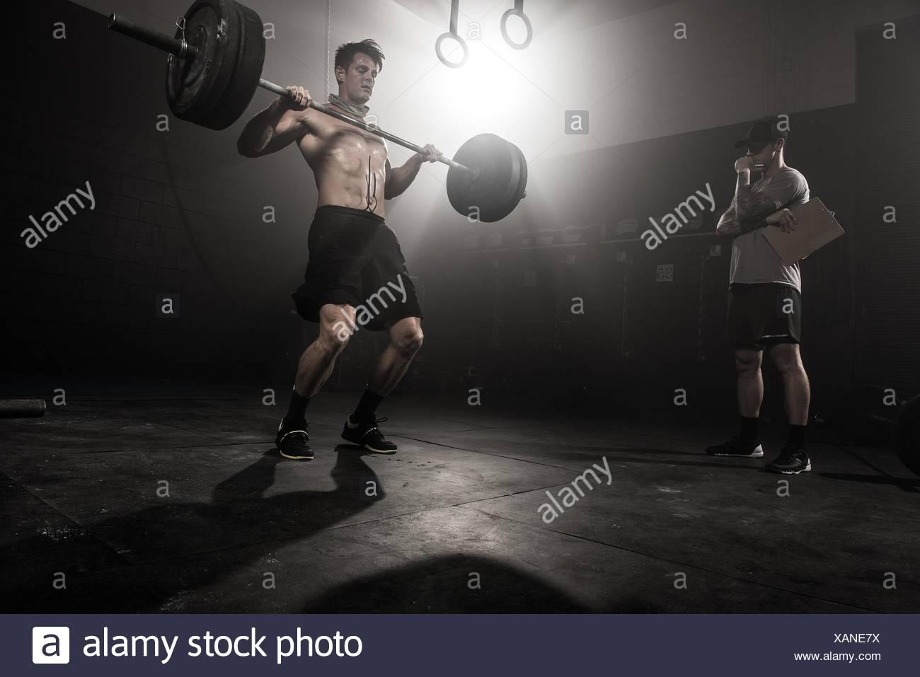 Mitad hombre adulto levantamiento barbell, mientras formador mira bajo ángulo de visión Imagen De Stock