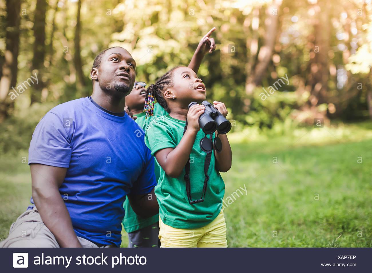 Padre joven con hijo e hija aves en eco campamento forestal Imagen De Stock