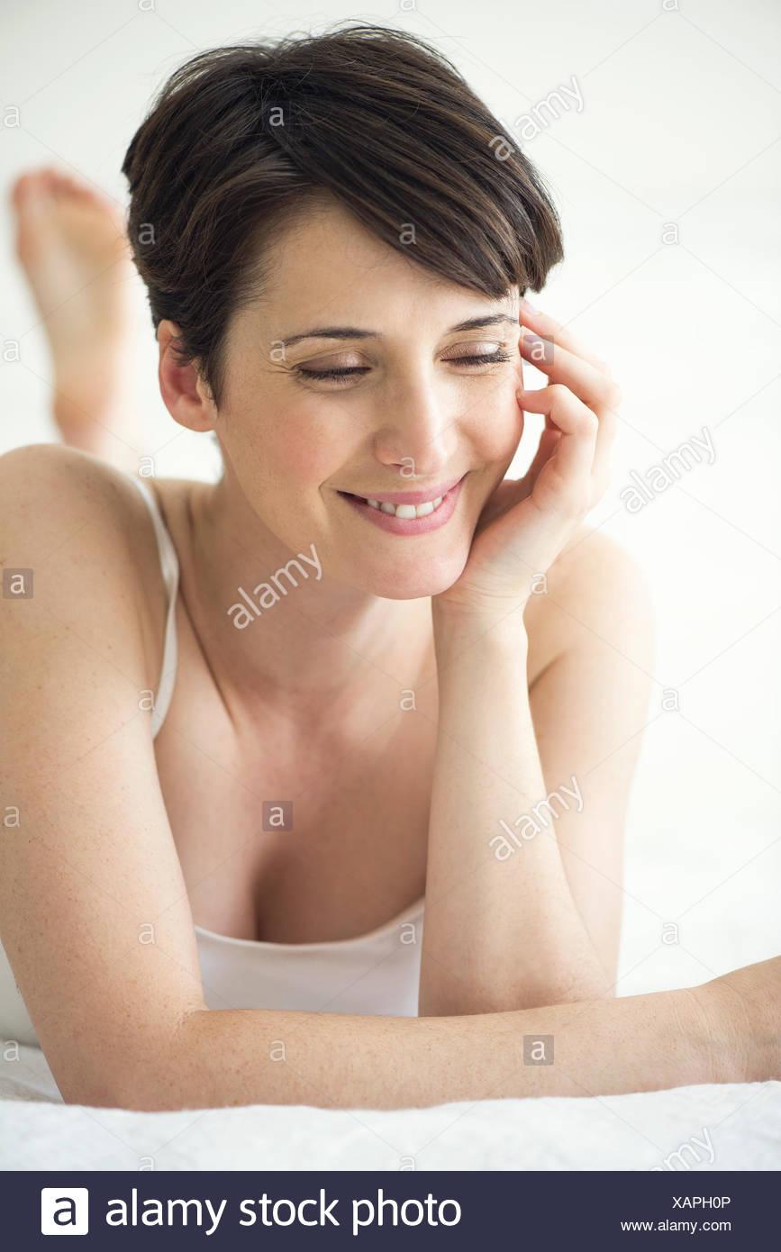 La mujer acostada en la cama con aspecto de alegría, Retrato Imagen De Stock