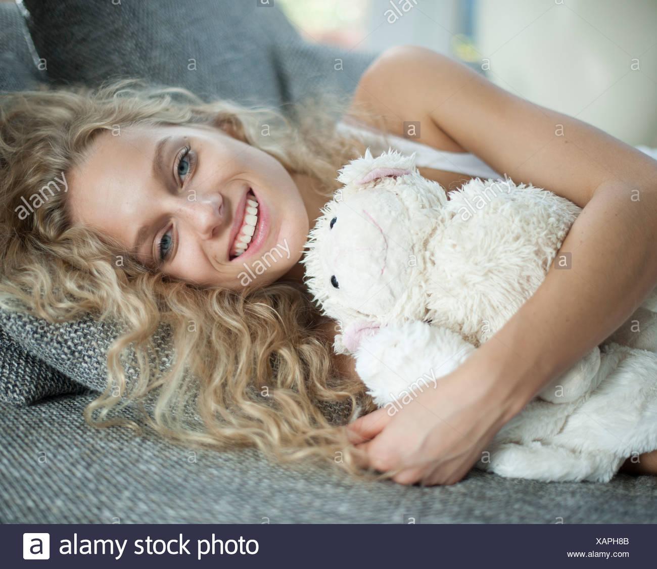 Retrato de mujer joven con osito tumbado en el sofá Imagen De Stock