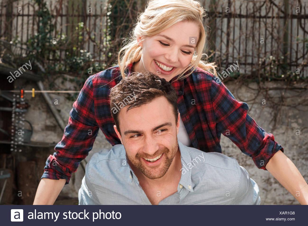 Hombre haciendo mujer sonriente piggyback Imagen De Stock