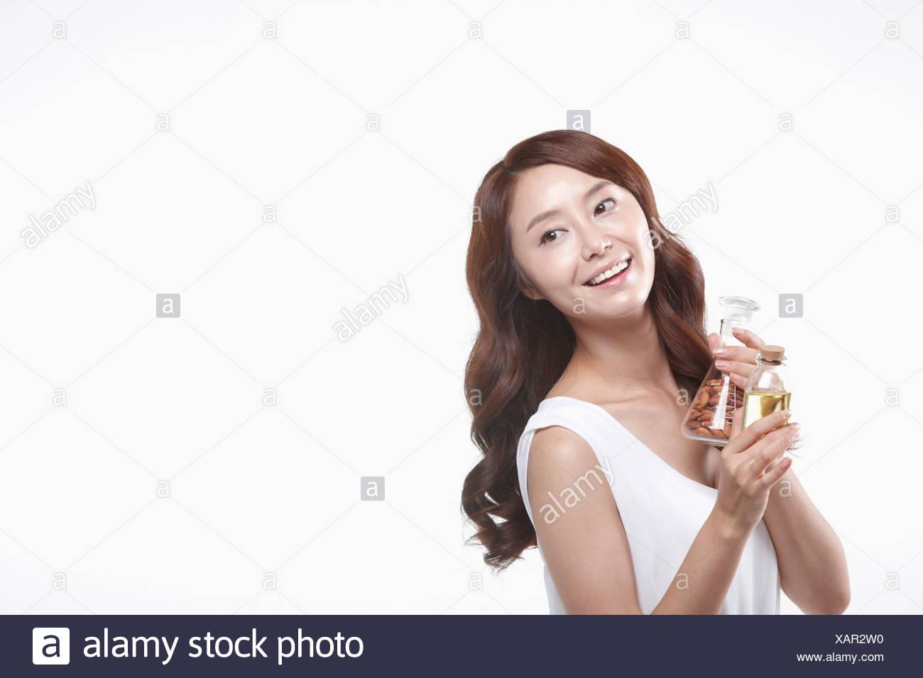 Una señora en vestido blanco sosteniendo una jarra con tuercas Imagen De Stock
