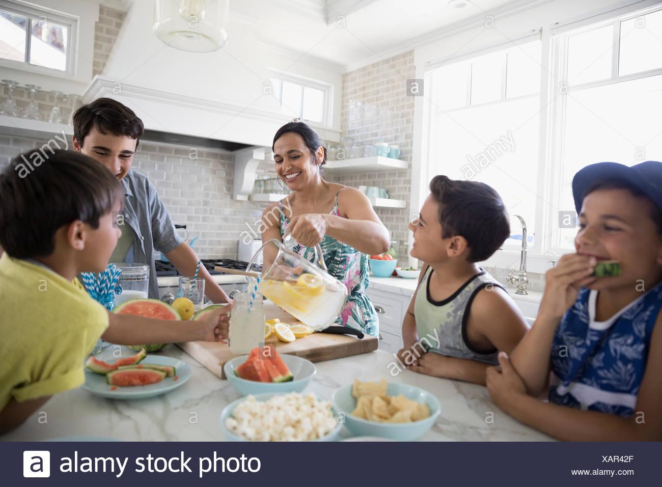 Madre vertiendo limonada para hijos en la cocina Imagen De Stock