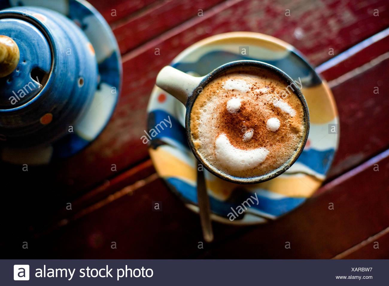 Cerrar foto de una taza de café expreso con una sonrisa y una cara hecha de espuma. Imagen De Stock