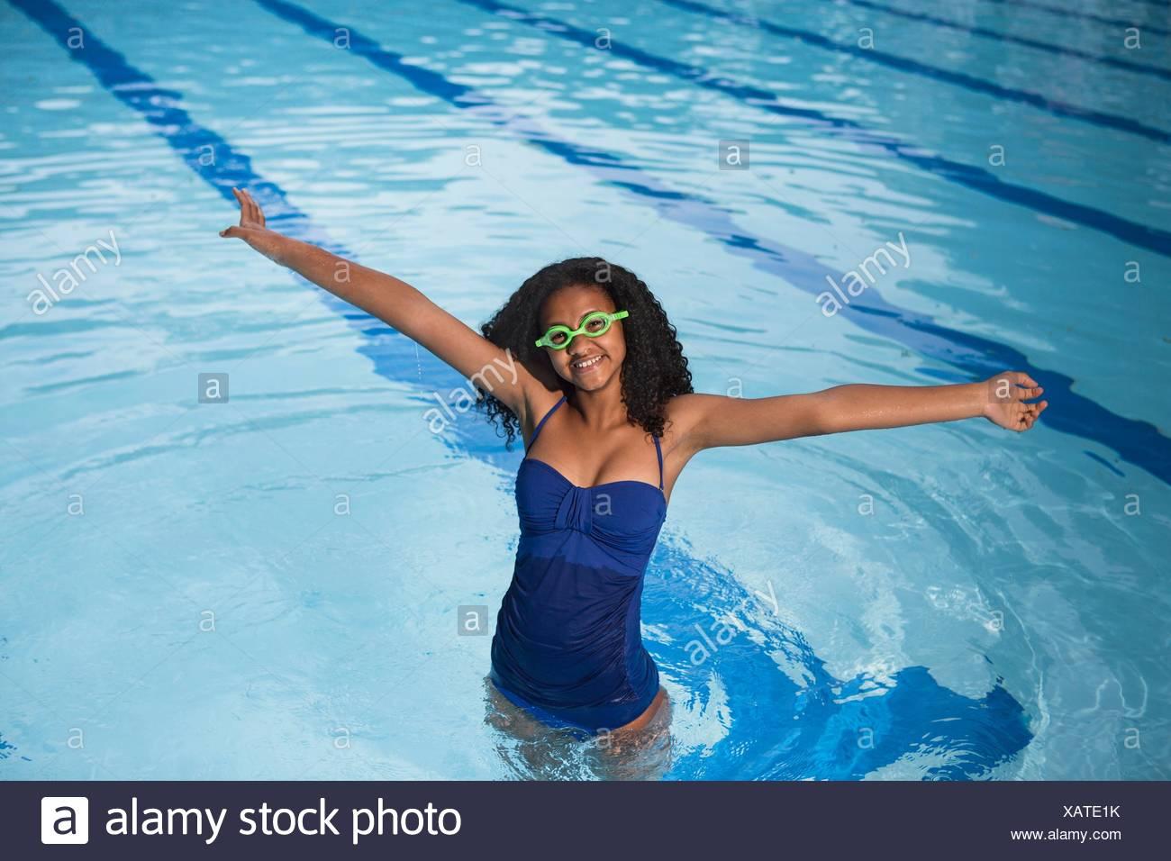 Retrato de niña de pie en la piscina llevar gafas de natación, con los brazos en alto, mirando a la cámara sonriendo Imagen De Stock