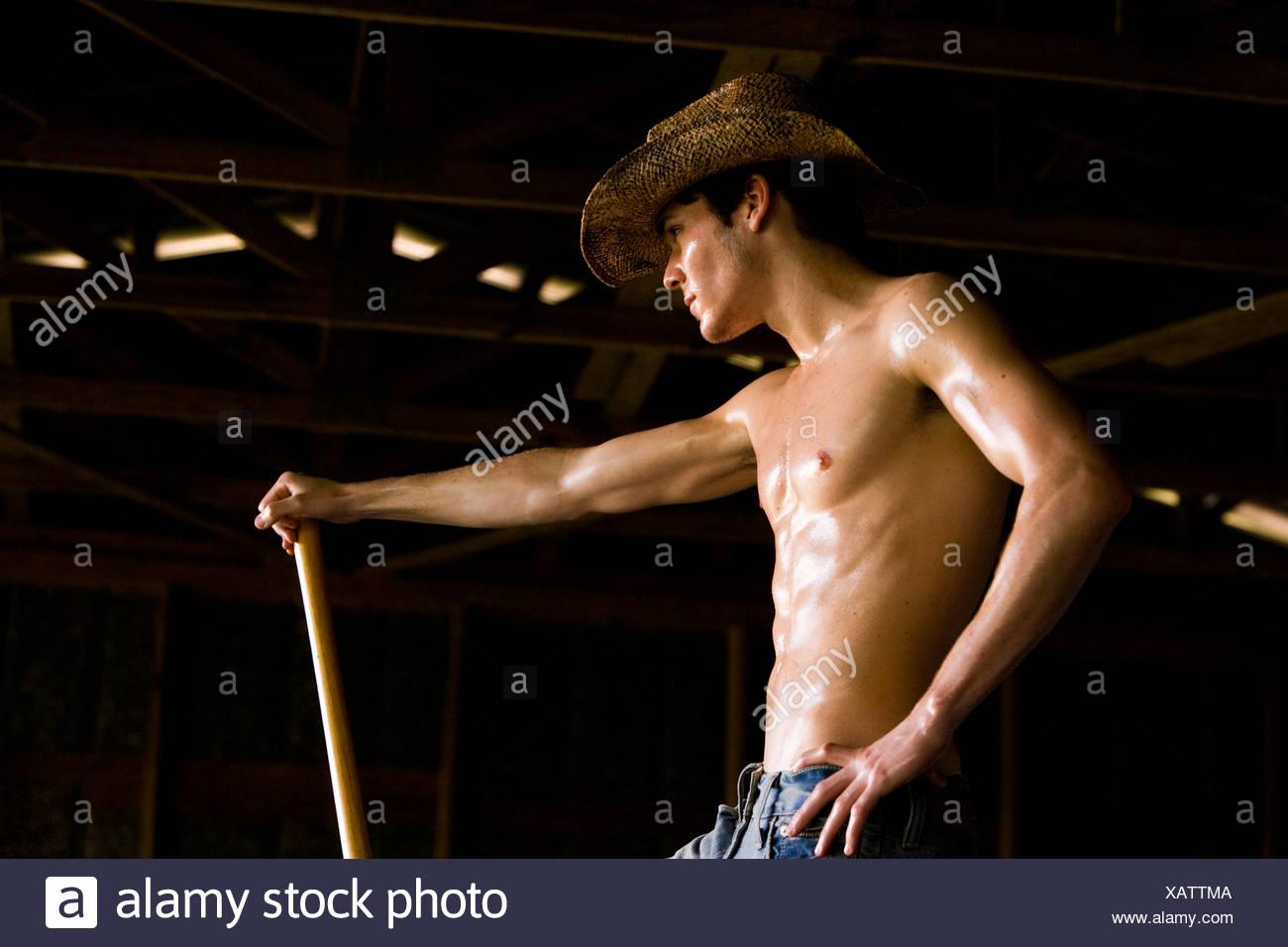 Joven sosteniendo la pala llevar sombrero de cowboy Imagen De Stock 2428d869cfc