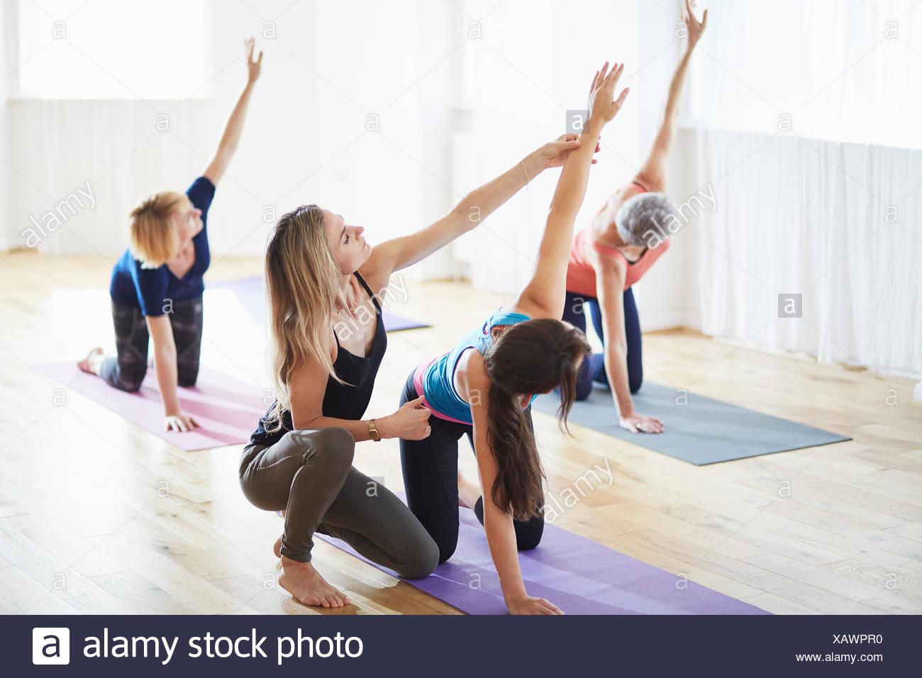 Las mujeres de rodillas y elevando los brazos en clase de pilates Imagen De Stock