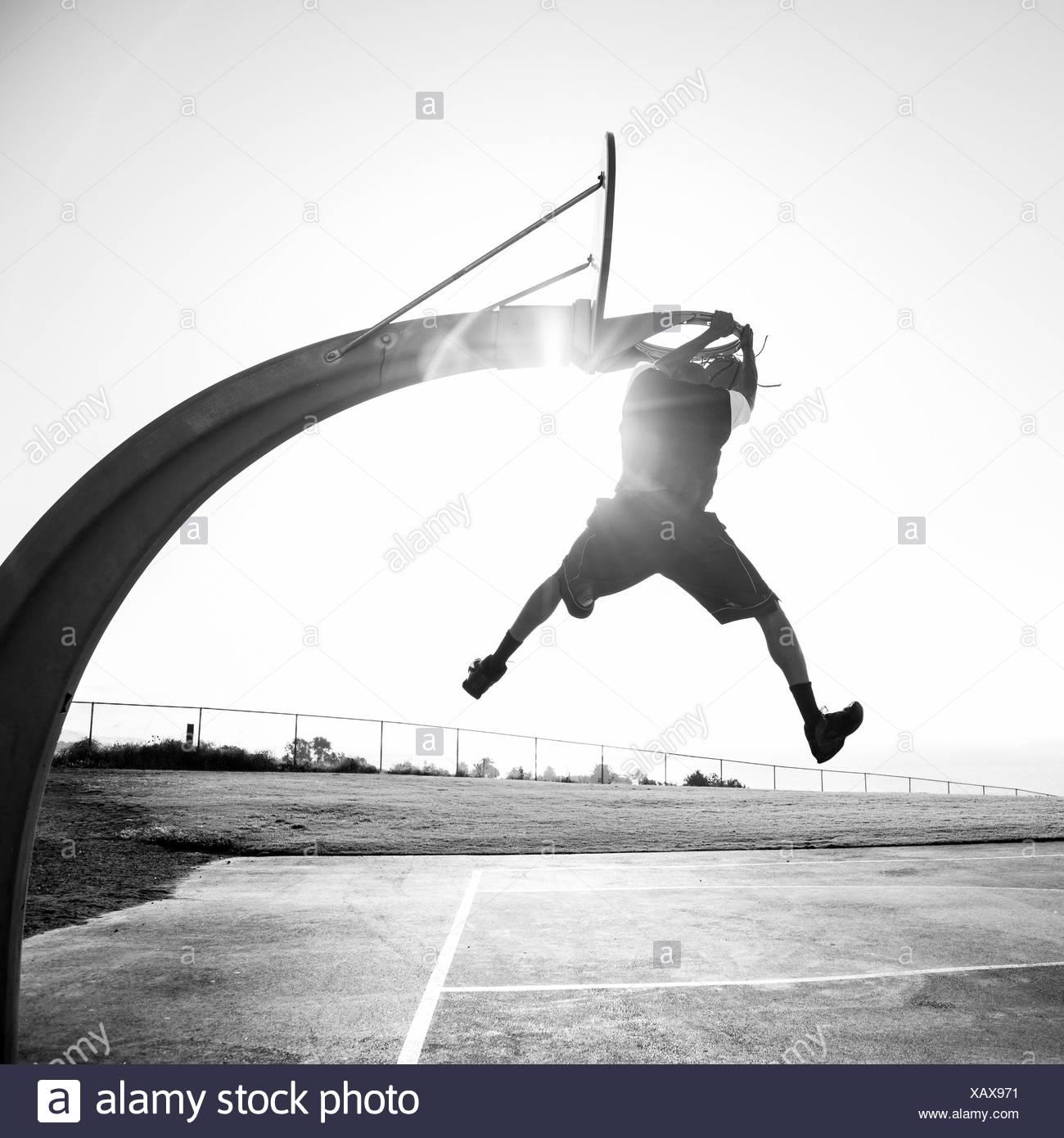 Joven Shooting Hoops en un parque, en Los Ángeles, California, Estados Unidos. Imagen De Stock