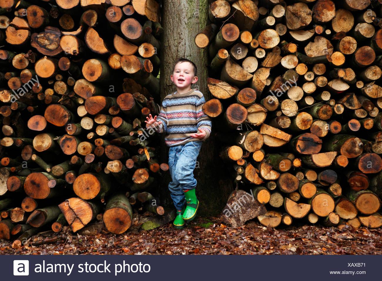 Muchacho por troncos de madera permanente Imagen De Stock