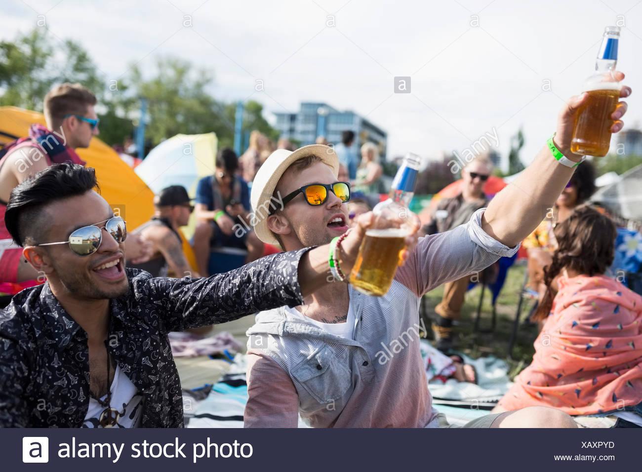 Los hombres jóvenes bebiendo cerveza vitoreando en festival de música de verano camping Imagen De Stock