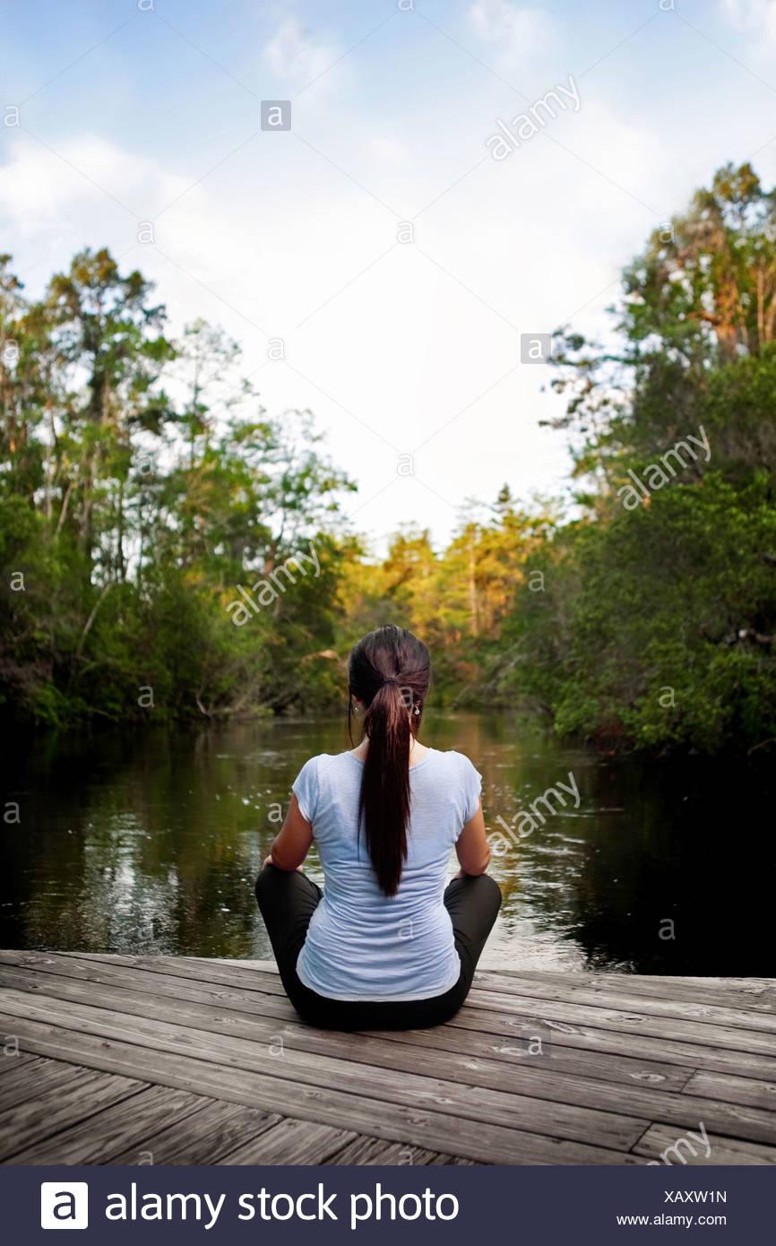 Mujer joven relajándose en un muelle mirando a través de un canal hacia los árboles lejanos Imagen De Stock