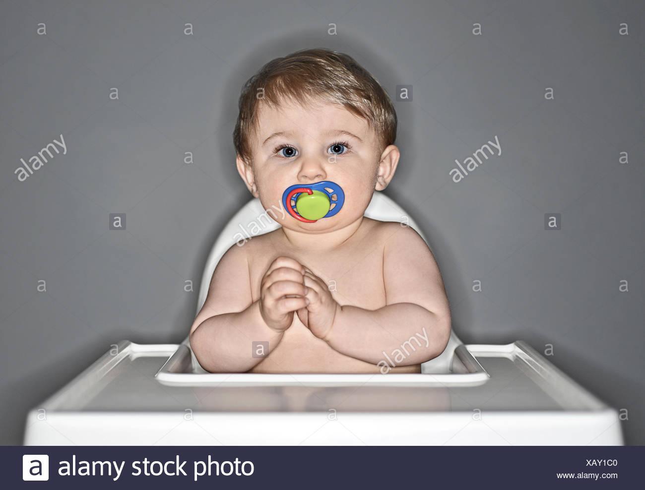 Contenido sentado en la Trona de bebé chuparse dummy Imagen De Stock
